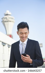 Traveler looking at cell phone message at airport