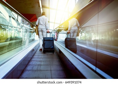 Traveler with luggage on moving walkway.Travel concept.