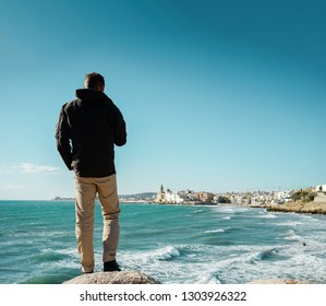 Traveler man from the back on the  sea coast, city skyline in the background