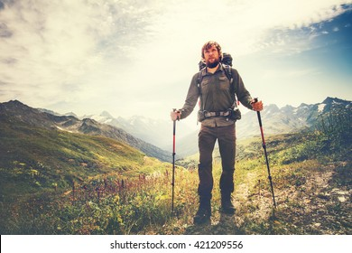 Traveler Man with backpack and trekking poles mountaineering Travel Lifestyle wellness concept mountains and clouds on background Summer adventure vacations outdoor