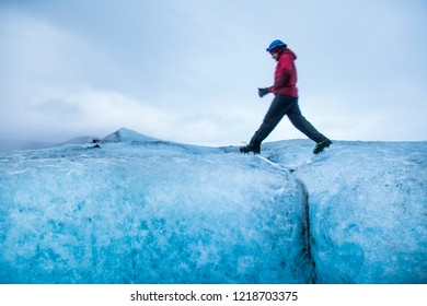 Traveler man crossing a small creek of melted glacier water, exploring Vatnajokull National Park, amazing nature of Skaftafell, Iceland.