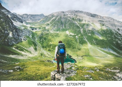 Traveler man hiking alone in mountains adventure active lifestyle traveling  summer vacations outdoor solitude harmony with nature hiker standing on cliff above lake landscape