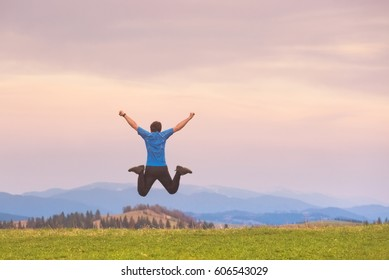Traveler Man jumping hands raised mountains landscape on background Lifestyle Travel happy emotions success concept summer vacations outdoor