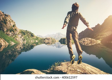 Traveler Man levitation jumping with lake and mountains on background Lifestyle Travel emotions concept outdoor