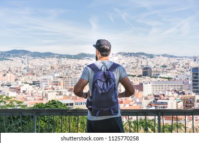 Traveler man looking on a big city, travel and active lifestyle concept.Bearded Tourist Man with backpack enjoy beautiful panoramic view of modern european city