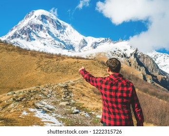 Traveler man points to the top of the mountain, standing back. Travel lifestyle, holiday vacation concept