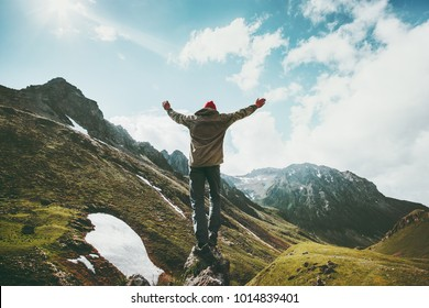 Traveler Man raised hands standing on cliff mountains adventure travel lifestyle concept summer vacations outdoor euphoria happy emotions