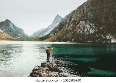 Traveler Man raised hands standing alone at sea stone Travel lifestyle survival emotional concept adventure outdoor active vacations wild scandinavian nature