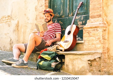 Traveler man reading book sitting outside old house with backpack and guitar - Young globetrotter relaxing at village alley - Concept of teenage freedom , holiday , vacation, trip  around the world