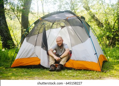Traveler man relax at camping tent outdoors on nature. Explorer, hiker travel in green summer forest and sit in tourist tent at sunny campsite.