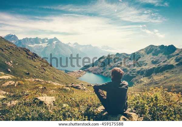 Traveler Man relaxing meditation with serene view mountains and lake landscape Travel Lifestyle hiking concept summer vacations outdoor