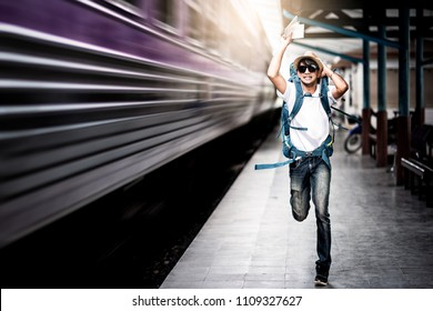 Traveler man running after a moving train from a railway station