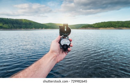 Traveler man searching direction with a compass on a coastline near a lake in the mountains. Point of view shot.