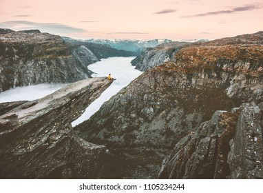 Traveler man sitting alone on the edge of Trolltunga cliff traveling in Norway adventure lifestyle extreme trip vacations outdoor mountains over clouds landscape aerial view