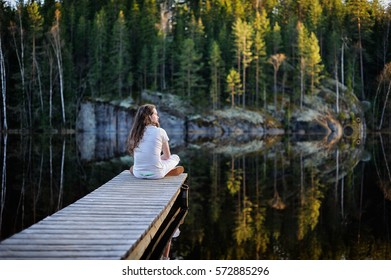 Traveler man sitting and meditating on a pontoon by a lake at the morning