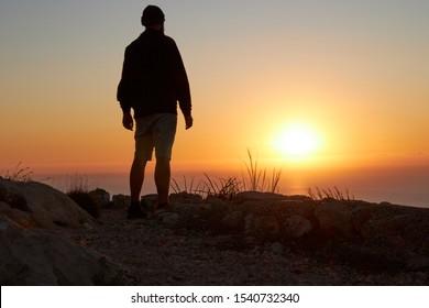 traveler man at sunrise adventure concept