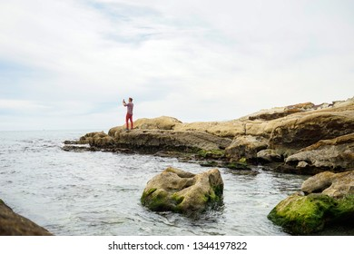 Traveler man taking photo with smartphone from the ocean rocky shore, foggy day