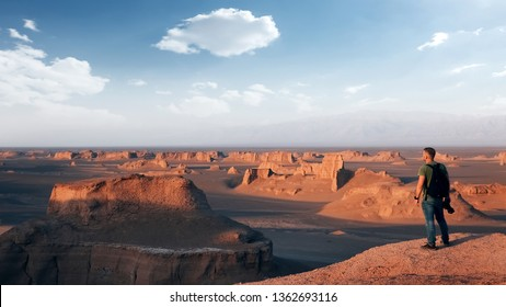 Traveler on the background of rocky formations in the Dasht e Lut desert. Nature of Iran. Persia.