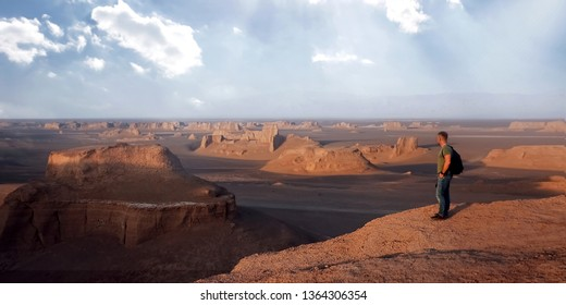 Traveler on the background of rocky formations in the Dasht e Lut desert. Nature of Iran. Persia. Banner design.