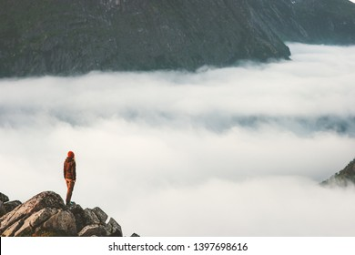 Traveler on cliff above clouds travel hike in mountains alone adventure extreme summer trip outdoor Norway vacations