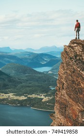 Traveler on cliff mountains over fjord enjoying Norway landscape Travel Lifestyle success motivation concept adventure active vacations outdoor