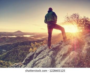 Traveler on mountain summit enjoying aerial view over misty countryside. Travel Lifestyle success adventur