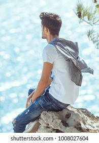 Traveler on the rocks near the sea looking at camera. Summer Travel Vacation. Handsome young caucasian tourist man in casual clothes outdoors on the nature.