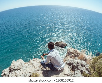 Traveler on the rocks near the sea looking far away at horizon. Summer Travel Vacation. Handsome young caucasian tourist man in casual clothes outdoors on the nature. Wide angle photo on fish eye lens