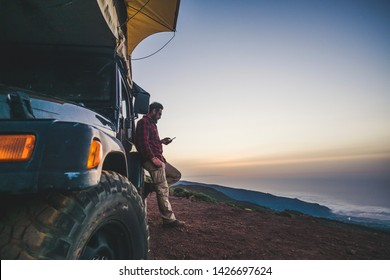 Traveler people with car and camping concept - lonely man use cellular phone to connect to internet outside his vehicle - mountain and nature outdoor around - enjoying freedom and alternative vacation