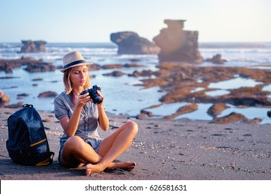 Traveler and photographer. Pretty young woman holding camera on beautiful ocean beach.
