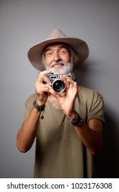 Traveler and photographer. Studio portrait of handsome senior man with gray beard and hat holding photocamera.