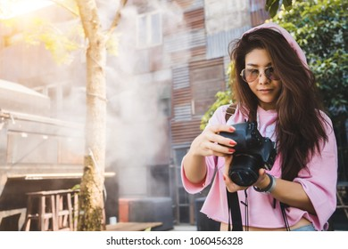 Traveler photography girl with dslr camera take photo. Young lady professional photographer looking pictures in dslr. Asian hipster female traveling concept. Photographer girl with dslr concept.