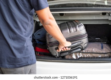 Traveler pick up a suitecase from the trunk of the car