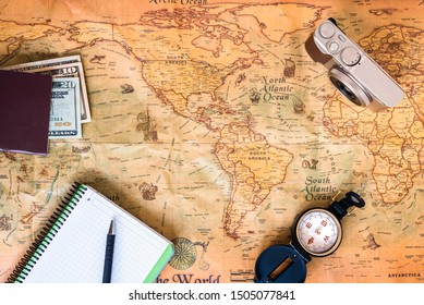 A traveler plans his trip around the world on an ancient  old map, while taking notes to get inspired.