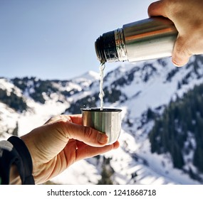 Traveler pouring tea from thermos to cup against winter mountain background.