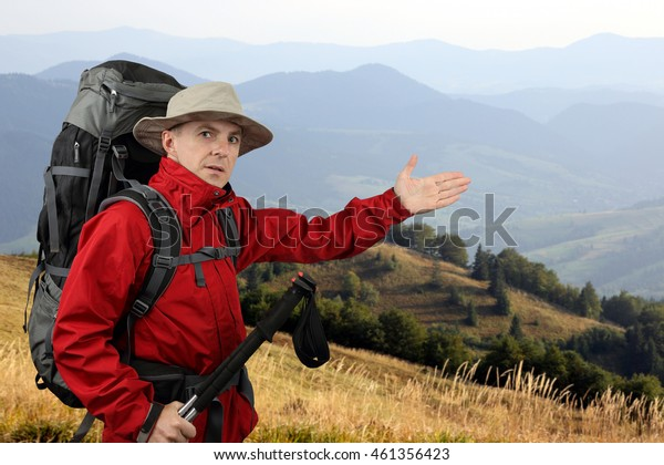 traveler in red jacket with backpack points into the distance hand being on the hillside