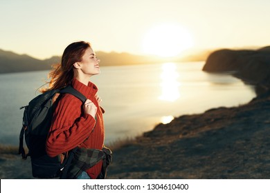 Traveler in a red sweater greets the dawn near the sea in the mountains
