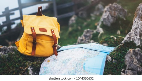 traveler relax holiday concept, view planning way road in trip vacation, hipster hiker tourist yellow backpack closeup and navigation map europe on background green nature, blurred panoramic landscape
