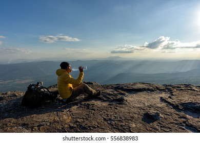 Traveler relaxing on the rock and drinking bottled water