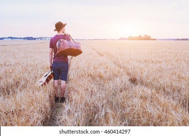traveler,  romantic travel background, young son leaving home, man with guitar and road bag walking at sunset field