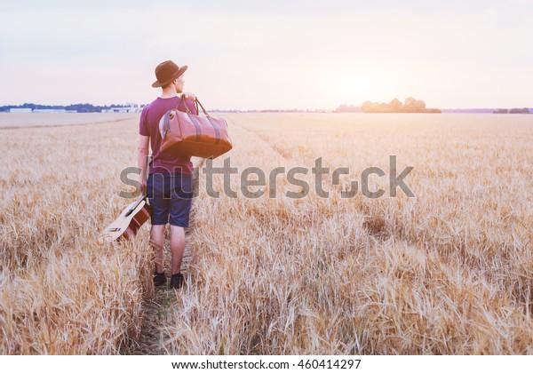 Reisende, romantischer Reisehintergrund, junger Sohn, der das Haus verlässt, Mann mit Gitarre und Straßentasche, der bei Sonnenuntergang geht