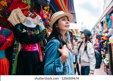 traveler shopping in the traditional market and thinking what to buy for souvenirs in Mexican street. beautiful tourist being attracted by the beauty of the blue sky. tourists standing in outdoor.