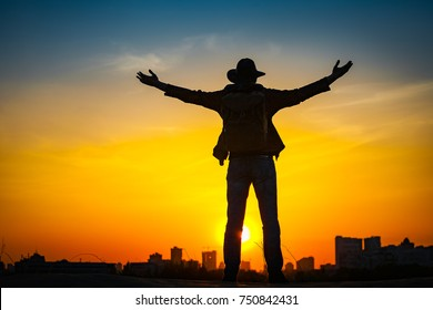 Traveler silhouette with a backpack and cowboy hat stand on hill top. City in the background. Sun sets over horizon. Man looks ahead, raise his arms up. Travel, holidays, advanture, success concept.