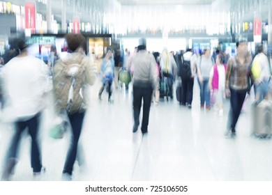 Traveler silhouettes in motion blur, airport interior, blue toned image