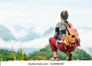 Traveler sits at the edge of the road and looks at a mountain landscape in clouds.