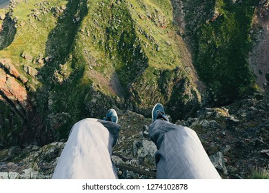 Traveler sits on the edge of a cliff.  Man feet in the background of a mountain landscape. Concept of adventure and lifestyle achievements