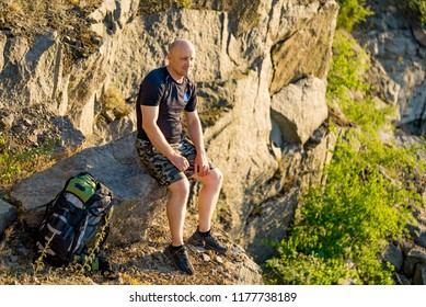 a traveler sits on a stone with a backpack near his legs on the background of the rocks. A man enjoys nature around him