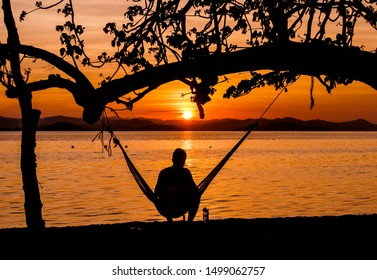 Traveler sits in seaside hammock and watches a beautiful sunrise
