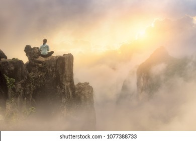 Traveler sitting on cliff enjoying view on mountains and clouds to sunrise.North VietnamMountains landscape, travel to Asia, summer holiday concept