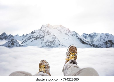 Traveler sitting on mountain peak, POV view on great winter mountains above the cloud and hiking boots. Legs of close up on background of rock snowy landscape